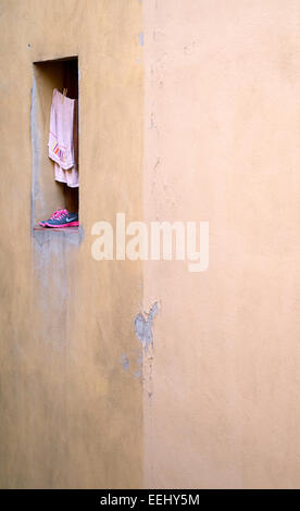 Clothing (pink towel and Nike trainers) drying in a window in a side street of Bologna ,Italy. - Stock Image