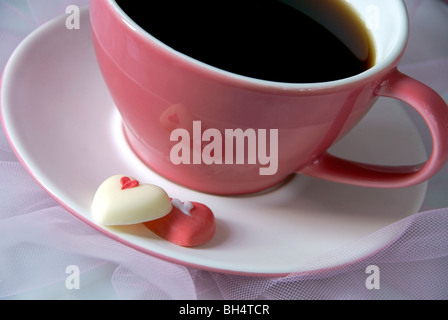 Pink coffee cup with chocolate hearts - Stock Image