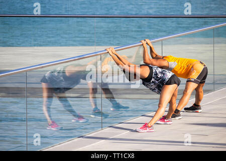 Male and female jogger stretching - Stock Image