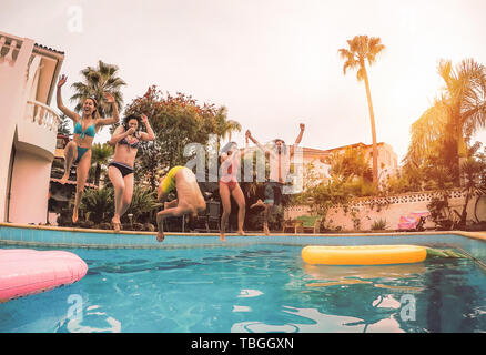 Group of happy friends jumping in pool at sunset time - Millennial young people having fun making party in exclusive resort tropical - Stock Image