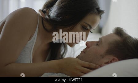 Close up profile of smiling happy couple laying on bed - Stock Image