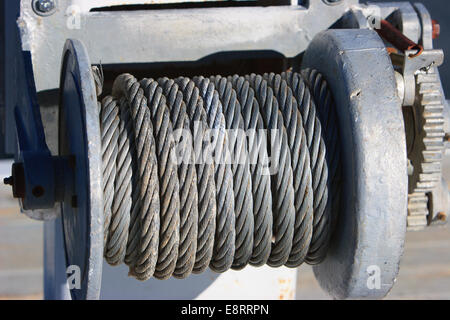 An industrial winch at a dock meticulously wrapped with thick cable - Stock Image