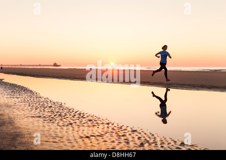 Female jogger at beach - Stock Image