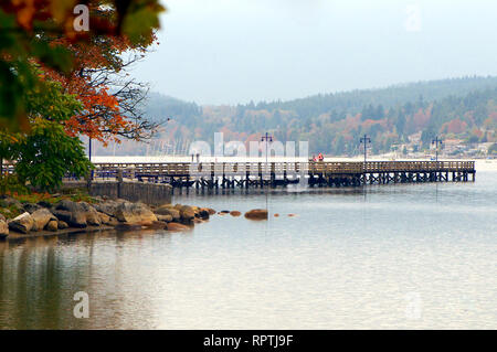 A scenic view of Rocky Point pier jutting out into Burrard Inlet with fall colours. - Stock Image