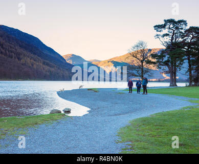 People enjoying a pleasant walk along a footpath alongside the popular Buttermere Lake in the Cumbrian lake district England UK - Stock Image