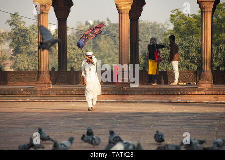 An Indian worker, dressed in white is sweeping the courtyard of the Jama Masjid in New Delhi. - Stock Image