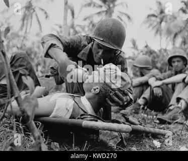 US Navy corpsman gives a drink to wounded Marine on Guam, July 1944, during World War 2.  (BSLOC_2017_20_187) - Stock Image
