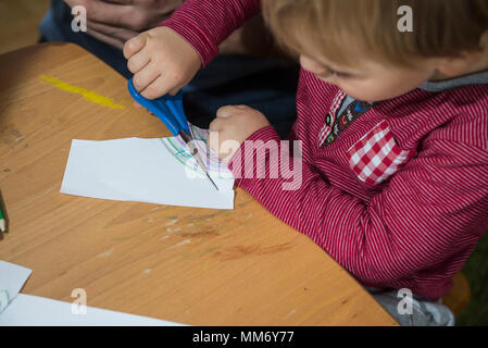Close up of a little boy cutting a paper with scissor, Munich, Germany - Stock Image