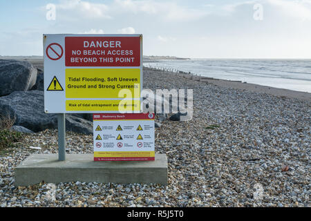 RSPB Medmerry Nature Reserve by the coast at Medmerry, West Sussex, UK. Danger signs on the shingle beach. - Stock Image