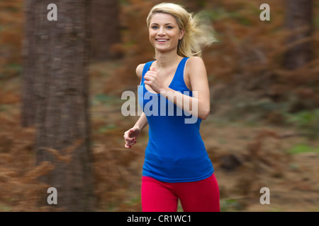 Smiling woman running in woods - Stock Image