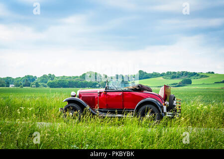 Red veteran car on a countryside road in the summer in a beautiful rural landscape - Stock Image