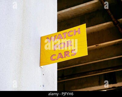 Caution sign warning to watch for cars on wall of a car park or urban parking garage in Montgomery Alabama, USA. - Stock Image