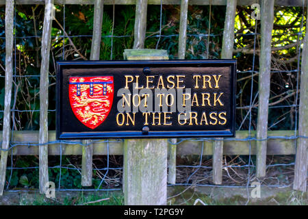 Parking Sign Please Try Not To Park on the Grass black with gold lettering and the crest of the Duchy of Lancaster in Goathland North Yorkshire - Stock Image