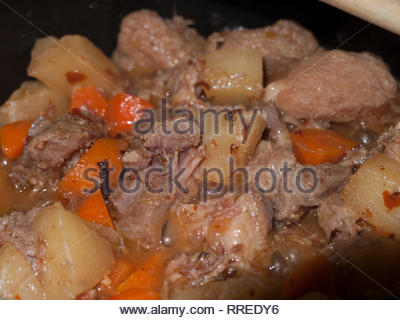 A pot of pork, carrot, and pineapple stew is cooking. - Stock Image