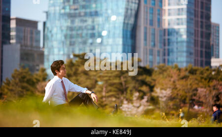 Businessman resting at park during daytime - Stock Image