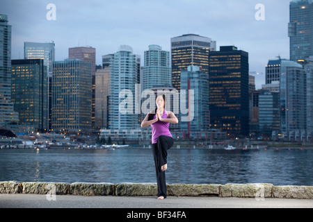 A young woman does yoga, the Vrksasana Tree Pose, with Vancouver skyline beyond, British Columbia, Canada - Stock Image
