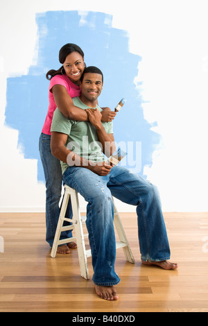 Portrait of African American male and female couple next to half painted wall - Stock Image