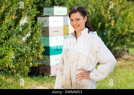 Portrait Of Confident Female Beekeeper At Apiary - Stock Image
