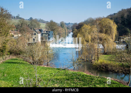 A sunny view of the Avoncliff weir from the Avoncliff aqueduct in Wiltshire UK. To the left is the old north mill in the middle of being refurbished. - Stock Image