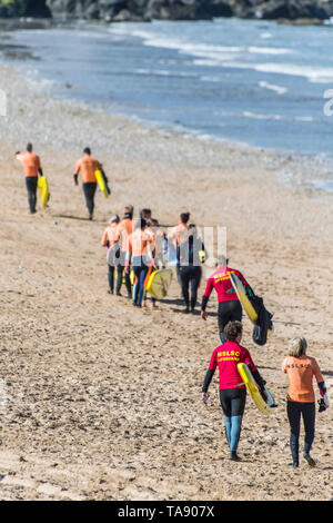 NSLSC members of a Surf Rescue training session with their instructors on Fistral Beach in Newquay in Cornwall. - Stock Image