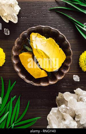 Yellow Jasper with Smoky Quartz and Mums on Dark Wood - Stock Image