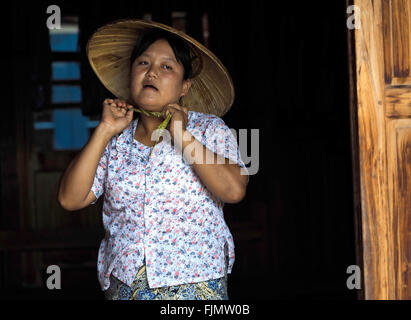Asian Woman puts on her 'sun hat', Myanmar - Stock Image