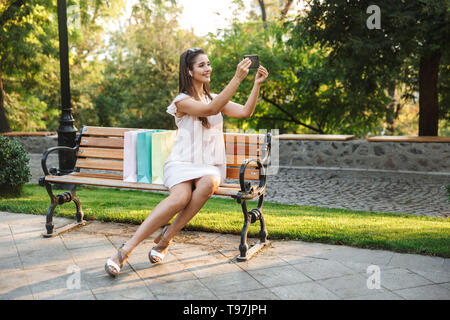 Portrait of a beautiful young woman wearing dress sitting on a bench outdoors, carrying shopping bags, taking a selfie - Stock Image