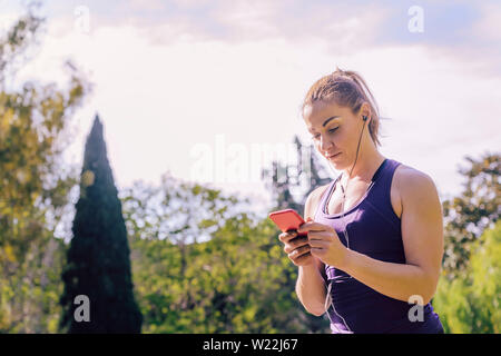 attractive blonde sports woman checking her phone app before running outdoors at park, fitness accessories - Stock Image