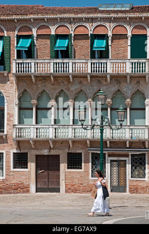 Elegant traditional brick buildings with beautiful balconies and stylish street lamp stand in Campo San Stefano - Stock Image