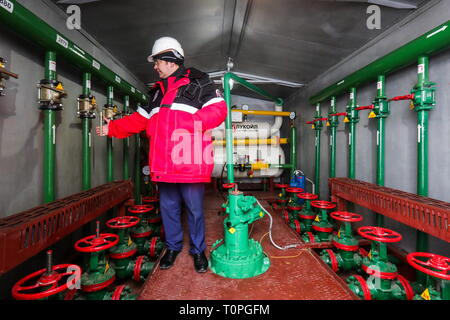KOGALYM, RUSSIA – MARCH 21, 2019: A worker at a measuring unit at the Yuzhno-Yagunskoye oil field developed by Kogalymneftegaz, a subsidiary of the Lukoil-West Siberia oil and gas company. Vyacheslav Prokofyev/TASS - Stock Image