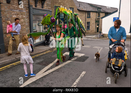 Large green praying mantis an automaton part of an art project being paraded around the town centre of Hay on Wye Powys Wales UK - Stock Image