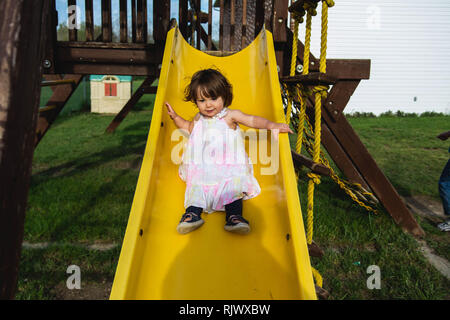 A 2 year old toddler girl slides down a slide at a playground during the summer. - Stock Image