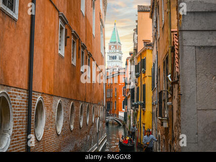 Two Gondoliers carry tourists on gondolas in a narrow canal with the Bell Tower in view in Venice, Italy. - Stock Image