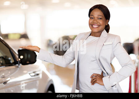 portrait of pretty vehicle saleswoman presenting new cars at showroom - Stock Image