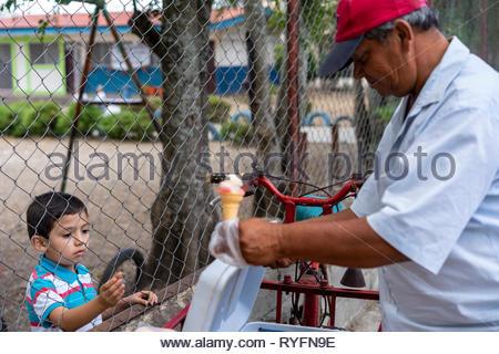 Street vendor near an elementary school hands a boy an ice cream cone - Stock Image
