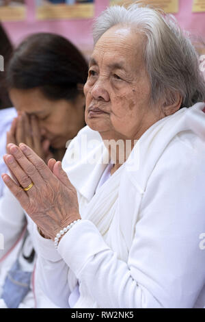 Devout Buddhist women in white praying & meditating at a service at a temple in Elmhurst, Queens, New York City. - Stock Image