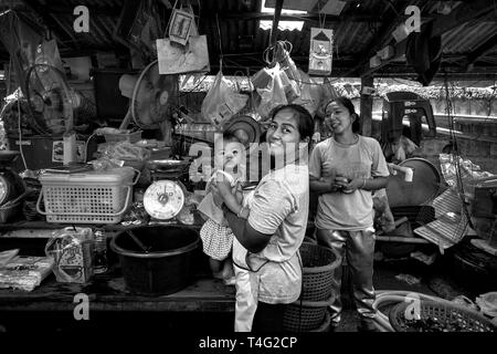 Working Mother and child at a Thailand market venue. - Stock Image