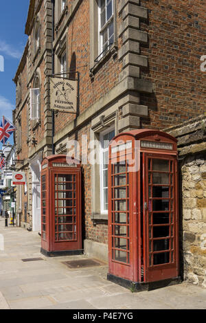 Two old red telephone boxes on the Market Square in the historic market town of Towcester, Northamptonshire, UK - Stock Image