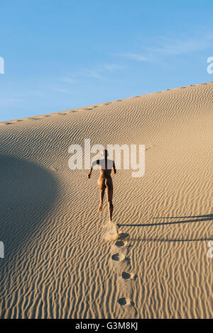 Nude woman running in desert leaving footprints - Stock Image
