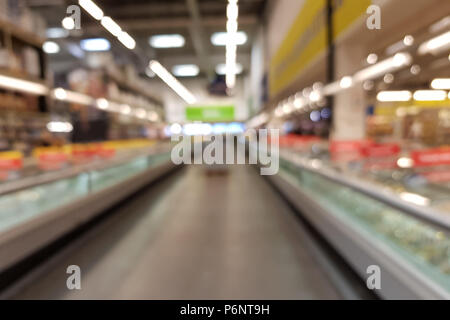 Blurred interior of a big store supermarket and shopping center with many shelves - Stock Image
