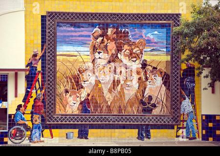Outdoor mural art San Antonio Texas shows workers hanging mural of African lion pride - Stock Image