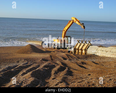 A Caterpillar Digger with Thorne Civil Engineering workers preparing to remove wooden moulding from new concrete - Stock Image