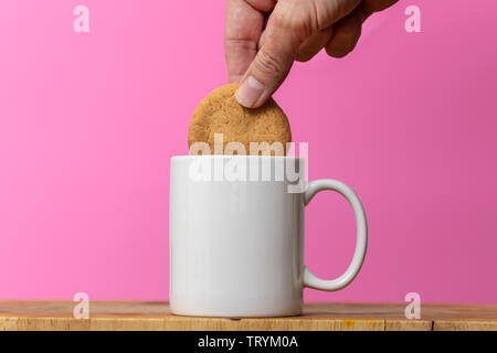 Dunking a biscuit into a mug of tea - Stock Image
