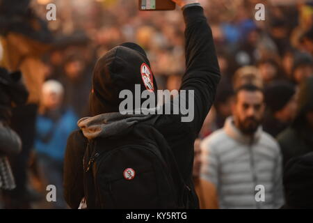 Vienna, Austria. 13th Jan, 2018. hooded protester takes a photo during an anti-government demonstration. Credit: - Stock Image