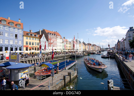 Nyhavn, Copenhagen with tourists taking a boat trip on a glorious summer's day - Stock Image