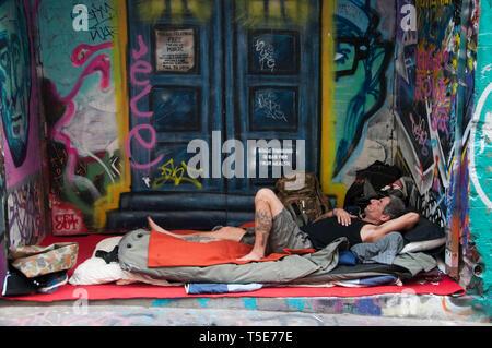 Homeless man oblivious to the street art in Hosier Lane, Melbourne - Stock Image