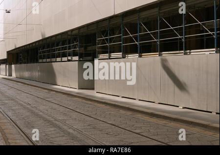 tramway tracks beside a building under renovation in Milan, Italy - Stock Image
