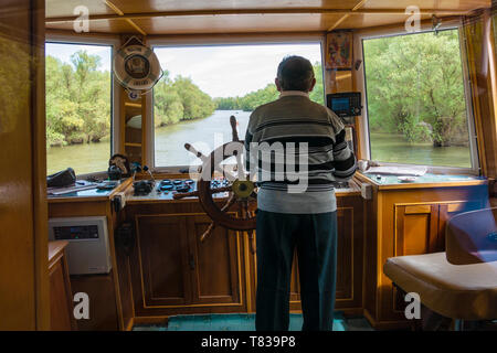 Nature Reserve Delta of the Danube River. Romania. April 20, 2019. A cruise ship swims along the river. The captain turns the rudder on the ship. - Stock Image
