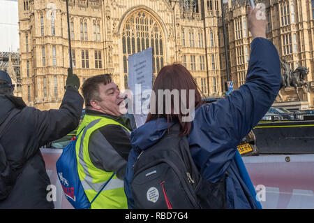 London, UK.  9th January 2019. Protests by stop Brexit group SODEM (Stand of Defiance European Movement) and pro-Brexit campaigners continue opposite Parliament. A man with a poster for the Guy Fawkes Movement promising civil war if we fail to leave the EU harasses a SODEM protester. Most other Brexiteers had come to support Brexit rather than cause trouble. Credit: Peter Marshall/Alamy Live News - Stock Image