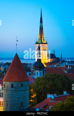 Tallinn city, view at night of the medieval Lower Town quarter with St Olaf's Church illuminated in the distance, Tallinn, Estonia. - Stock Image